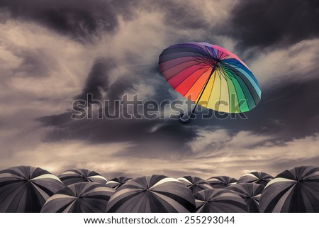 rainbow umbrella fly out the mass of black umbrellas - stock photo
