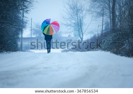 Rainbow umbrella holding by young girl who is walking in winter nature - original wallpaper - stock photo