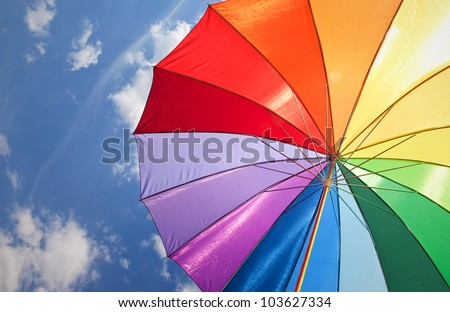 Rainbow umbrella on sky background - stock photo
