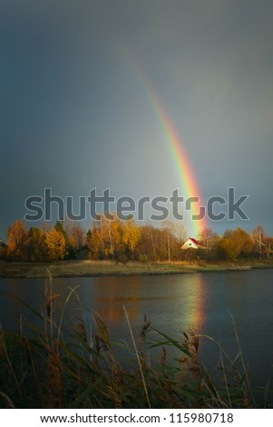 rainbow with reflection in the lake and the village house - stock photo
