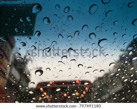 Raindrop on glass of car ,City life with traffic jam in rainy season