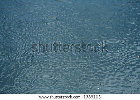 Raindrops forming concentric circles on the surface of a lake - stock photo