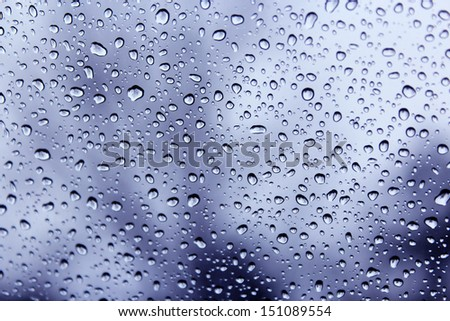 Raindrops on a car windscreen against a cloudy blue  sky in late winter  would be ideal for an abstract wallpaper design. - stock photo