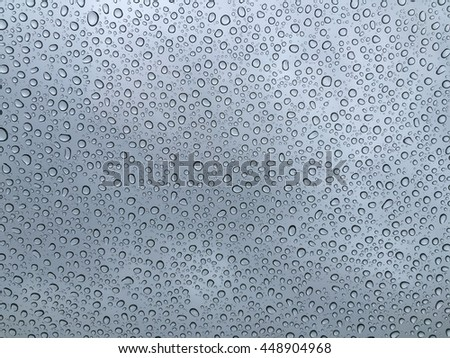 Raindrops on a car windscreen from inside car with a cloudy blue sky background - stock photo