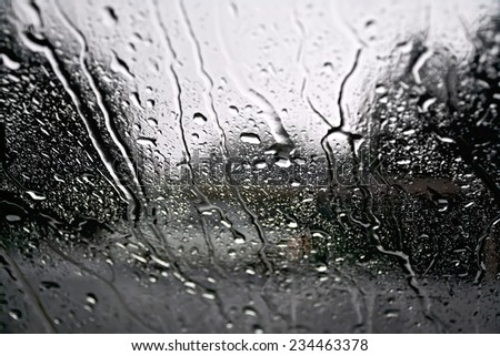 Raindrops on a glass window with blurry trees, road and gray car - stock photo