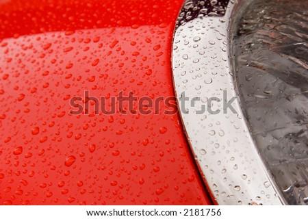 Raindrops on a red car headlight - stock photo