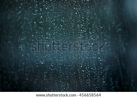 raindrops on a transparent window, gray-green color with blurred edges and focus in the center of the frame