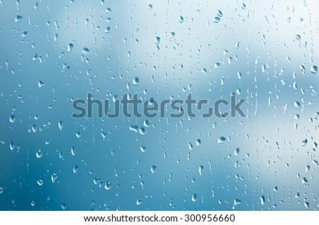 Raindrops on a window during bad, rainy weather. - stock photo