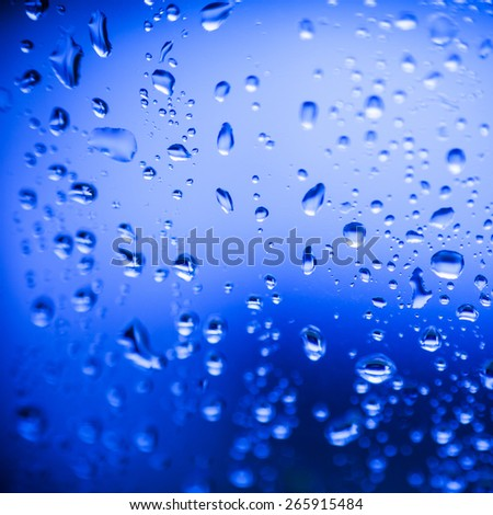 Raindrops on a window on a blue background - stock photo