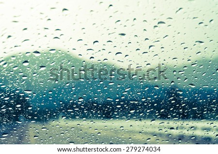 raindrops on auto glass with mountain view in vintage style - stock photo