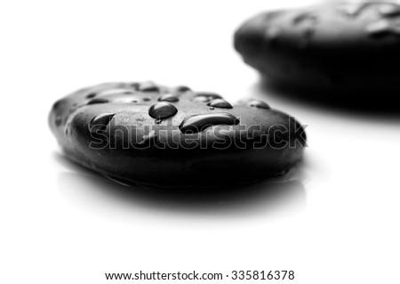 raindrops on black pebbles on white background - stock photo