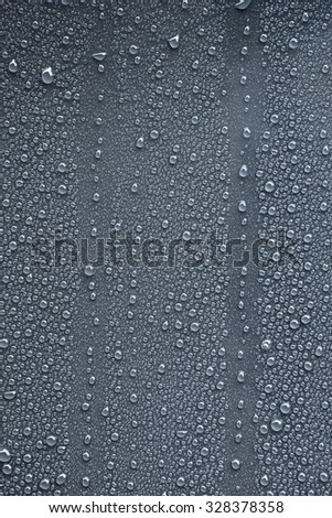 Raindrops on blue gray metal surface