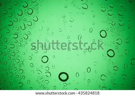 Raindrops on green glass. - stock photo