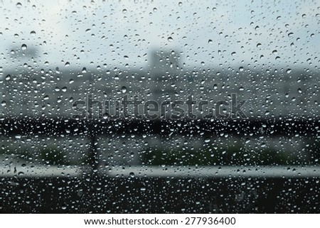 raindrops on the glass with blur building background. - stock photo