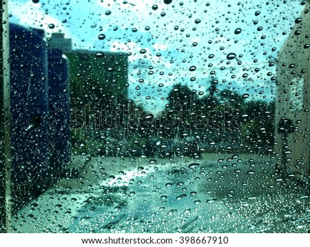 Raindrops on the windshield.blurred image of traffic view through a car windscreen covered in rain. - stock photo