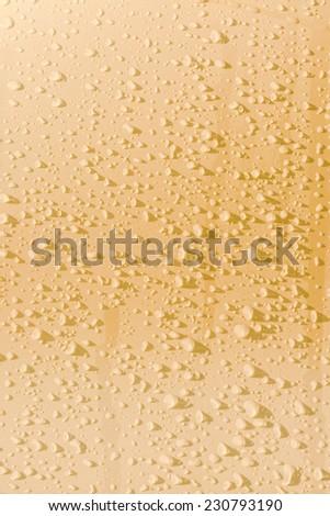 Raindrops on yellow metal surface - stock photo
