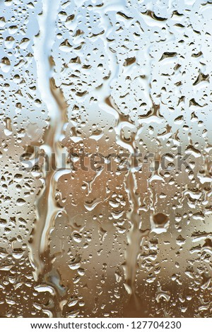 raindrops slide down the window glass, forming abstract figures - stock photo