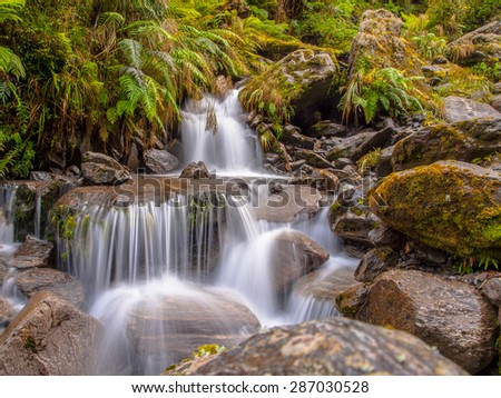 Rainforest waterfall long exposure image in lush tropical forest - stock photo