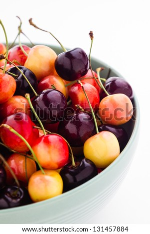 Rainier and black cherries mixed in a a green ceramic bowl. - stock photo