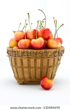 Rainier cherries sitting in a basket isolated on a white background. - stock photo