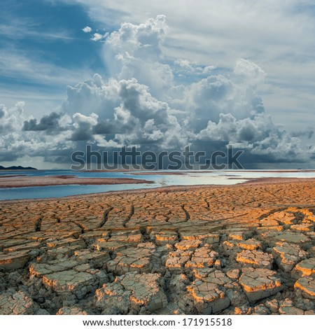 raining cloud over climate cracking ground  - stock photo