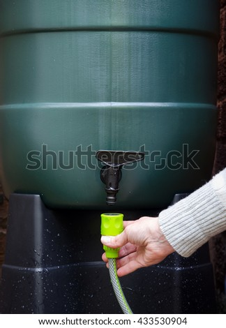 rainwater tank or water butt, woman connecting a hose to a rain collector to water garden. portrait. - stock photo