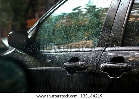 Rainwater trickling down the window pane of a black car waiting in the traffic at intense rain