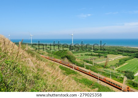 rainway at the coastline with wind turbine - stock photo