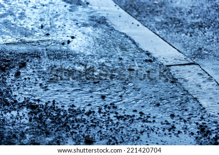 Rainy background with water on dark asphalt - stock photo