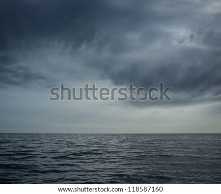 Rainy clouds over an ocean - stock photo