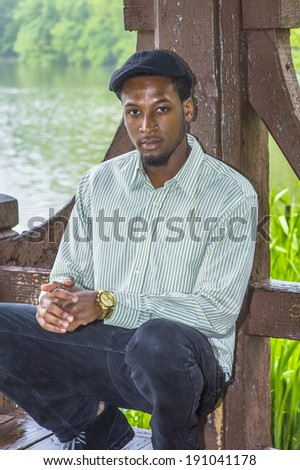 Rainy Day, a little foggy, wet feel. Dressing in a long sleeves shirt, a ivy cap,  a young handsome black guy is squatting by a lake in a raining, foggy day, charmingly looking at you.