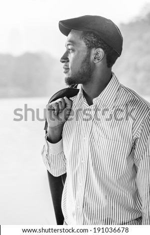 Rainy Day, a little foggy, wet feel. Wearing a long sleeves shirt, a ivy cap, taking off a jacket on his shoulder,  a young handsome black man is standing by a foggy lake, confidently looking forward.