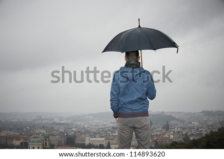 Rainy day in Prague - young man with umbrella - stock photo