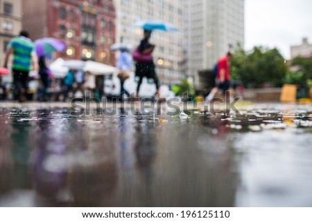 Rainy Day in the City with People Holding Umbrellas in the Background - stock photo