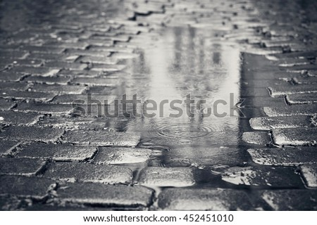 Rainy day. Reflection of the building in puddle on the city street during rain. - stock photo