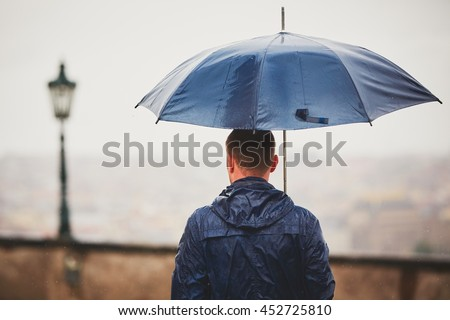 Rainy day. Young man is holding blue umbrella and walking in rain. Street of Prague, Czech Republic. - selective focus on person