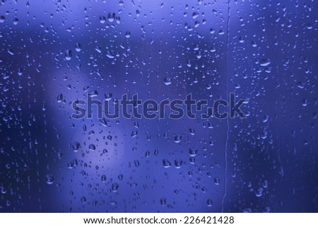 Rainy Days ,rain drops on glass window ,city lights  in the background blue