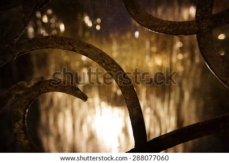 Rainy night background through the scrollwork with a vintage texture overlay. - stock photo