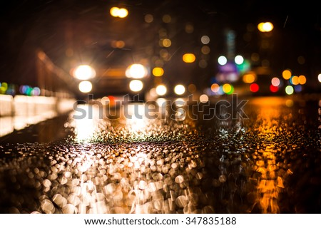 Rainy night in the big city, approaching headlights of car traveling along the avenue. View from the level of the curb on the road - stock photo