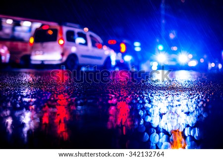 Rainy night in the big city, blinding headlights of an approaching car. View from the level of asphalt, image in the blue toning - stock photo