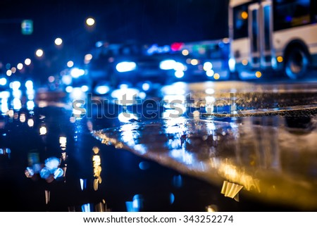 Rainy night in the big city, dense traffic at a busy intersection. View from puddles on the pavement level, in blue tones - stock photo
