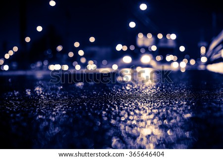 Rainy night in the big city, headlights of approaching cars on the highway. View from the level of the curb on the road, image in the yellow-blue toning - stock photo