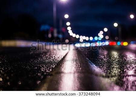 Rainy night in the big city, highway passing through a forest in the city park. View from the level of the dividing line, in blue tones - stock photo
