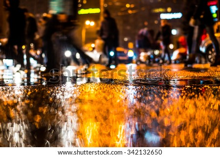 Rainy night in the big city, pedestrians cross the busy intersection. View from the level of a manhole on the pavement - stock photo