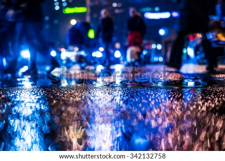 Rainy night in the big city, pedestrians cross the busy intersection. View from the level of a manhole on the pavement, in blue tones - stock photo