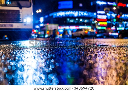Rainy night in the big city, riding the bus on the road in the light of shop windows. View from the level of asphalt, in blue tones - stock photo