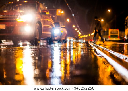 Rainy night in the big city, stream of cars traveling along the avenue and pedestrians on the road. View from the tram rail level - stock photo