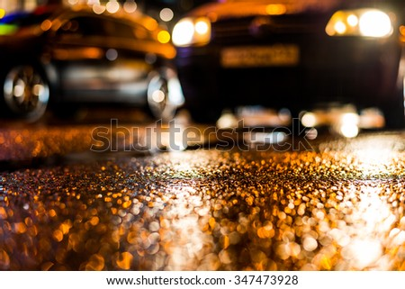 Rainy night in the big city, stream of cars traveling along the avenue. View from the level of asphalt