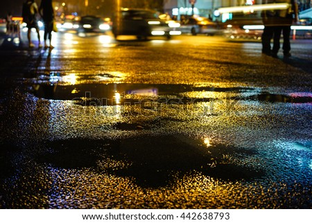 Rainy night in the big city, the light from the headlamps of vehicles approaching on the road. Close up view from the level of asphalt, focus on the asphalt