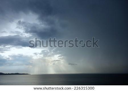 rainy sky with sun beams - stock photo